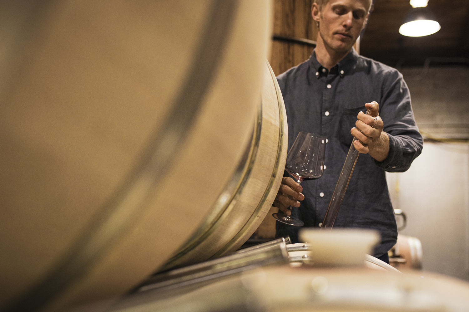 Close-up of winemaking team member taking a sample out of a barrel.